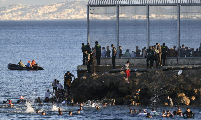 Spanish Guardia Civil officers try to stop people from Morocco swimming and entering into the Spanish territory at the border of Morocco and Spain, at the Spanish enclave of Ceuta, on May 17, 2021. (Antonio Sempere/Europa Press via AP)