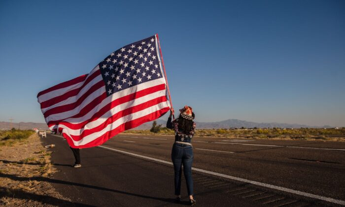 A woman waves a U.S. flag as a caravan of cars heads to a presidential debate watch party, in Golden Valley, Ariz., on Oct. 22, 2020. (Ariana Drehsler/AFP/Getty Images)