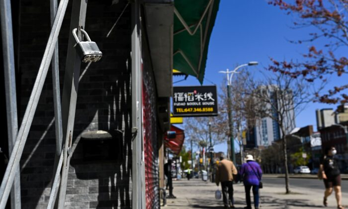 People walk past closed businesses on Spadina Avenue in Toronto on May 13, 2021, as stay-at-home orders continue across Ontario. (The Canadian Press/Nathan Denette)