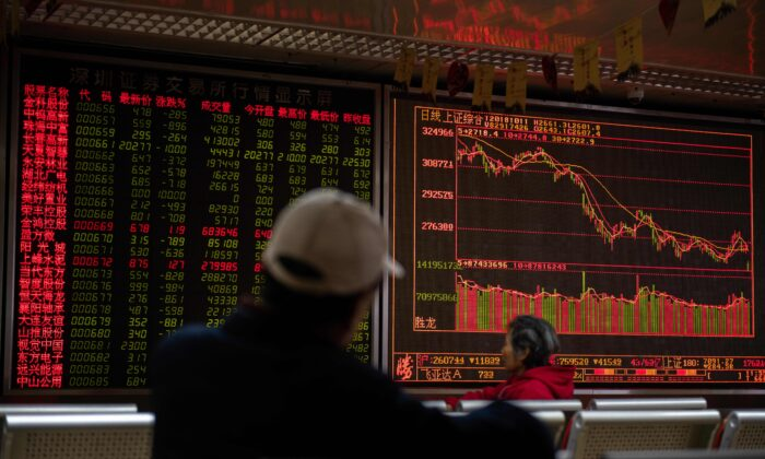 Investors look at stock price movements on a screen showing stock prices at a securities company in Beijing on Oct. 11, 2018. (Nicolas Asfouri/AFP via Getty Images)