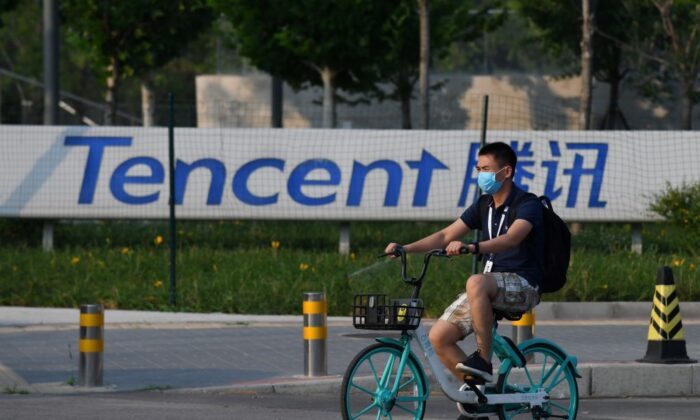 A man cycles past a Tencent sign, the parent company of Chinese social media giant WeChat, outside the Tencent headquarters in Beijing on Aug. 7, 2020. (Greg Baker/AFP via Getty Images)
