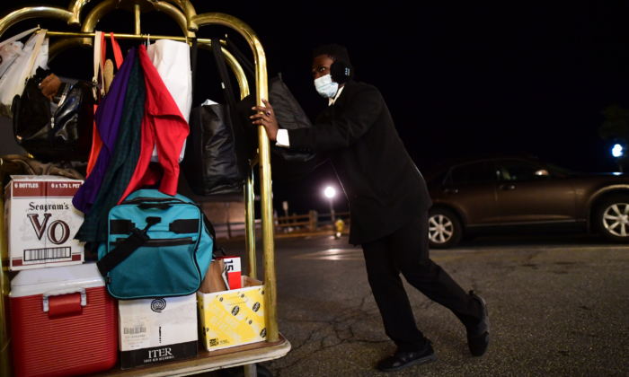 A porter pushes a cart of hotel guest bags into the lobby of the Boardwalk Plaza Hotel in Rehoboth Beach, Del., on Dec. 31, 2020. (Mark Makela/Getty Images)