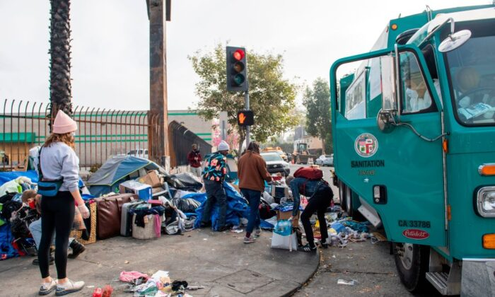 Activists help protect homeless from being displaced by street cleaning and power washing from the Los Angeles Sanitation service on February 8, 2021 in Hollywood, Calif. (Valerie Macon/AFP via Getty Images)