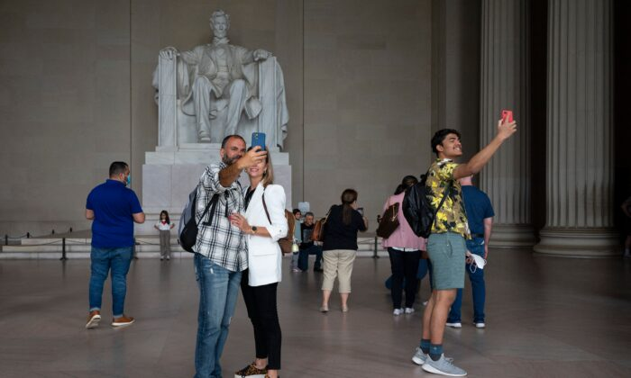 Tourists, some in face masks while others are not, visit the Lincoln Memorial in Washington, on May 14, 2021. (Jim Watson/AFP via Getty Images)