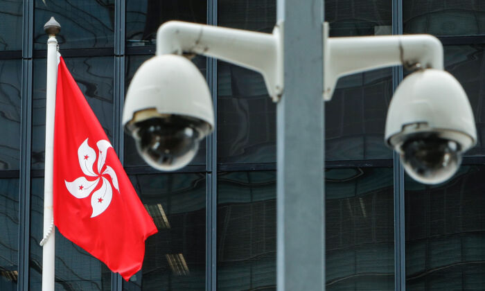 A Hong Kong flag is flown behind a pair of surveillance cameras outside the Central Government Offices in Hong Kong on July 20, 2020. (Tyrone Siu/Reuters)