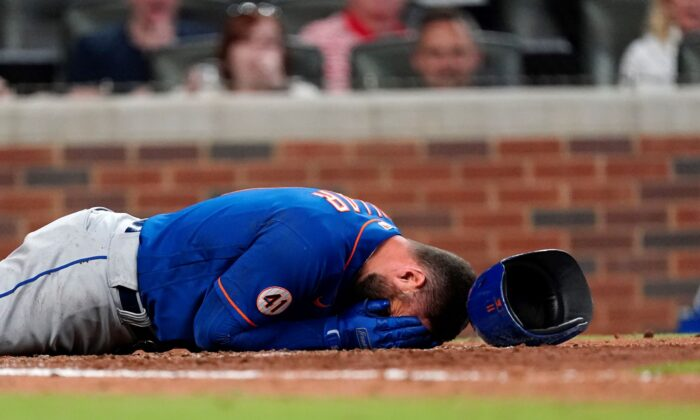 New York Mets' Kevin Pillar lies on the ground after being hit in the face with a pitch from Atlanta Braves pitcher Jacob Webb in the seventh inning of a baseball game in Atlanta, Ga., on May 17, 2021. (John Bazemore/AP Photo)