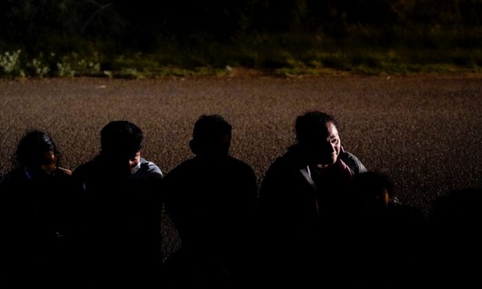 A group of migrants, mainly from Honduras and Nicaragua, wait along a road after turning themselves in upon crossing the U.S.-Mexico border in La Joya, Texas on Monday, May 17, 2021. (Gregory Bull/AP Photo File)