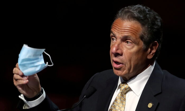 New York Governor Andrew Cuomo holds a protective mask as he speaks while making an announcement at a news conference from the stage at Radio City Music Hall in Manhattan in New York City, New York, on May 17, 2021. (Mike Segar/File Photo/Reuters)