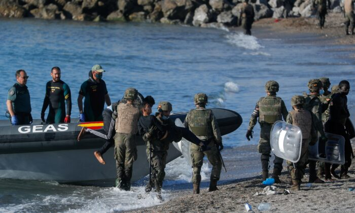 Spanish soldiers help Moroccan citizens at El Tarajal beach, near the fence between the Spanish-Moroccan border, after thousands of migrants swam across the border, in Ceuta, Spain, on May 19, 2021. (Jon Nazca/Reuters)