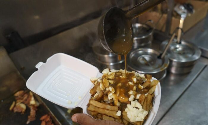 A cook prepares a poutine at La Banquise restaurant in Montreal on Tuesday, May 18, 2021. The Quebec dairy industry trying to get a protected trademark for the popular Quebecois dish. (Paul Chiasson/The Canadian Press)
