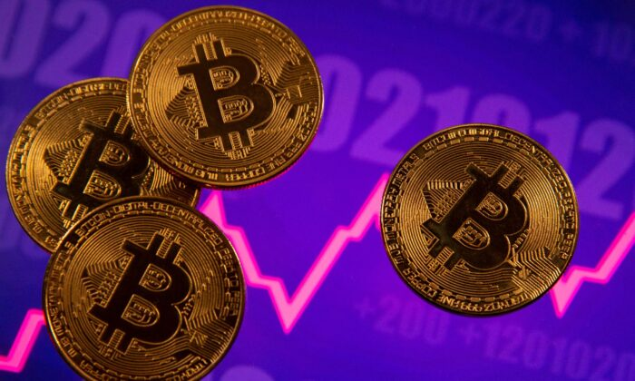 A representation of virtual currency Bitcoin is seen in front of a stock graph in this illustration on March 15, 2021. (Dado Ruvic/Reuters)