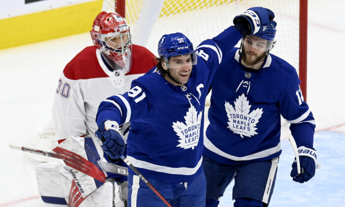 Toronto Maple Leafs center John Tavares (91) celebrates his goal with Alex Galchenyuk (12), in front of Montreal Canadiens goaltender Cayden Primeau (30) during the first period of an NHL hockey game in Toronto, Canada, on May, 6, 2021. (Frank Gunn/The Canadian Press via AP)
