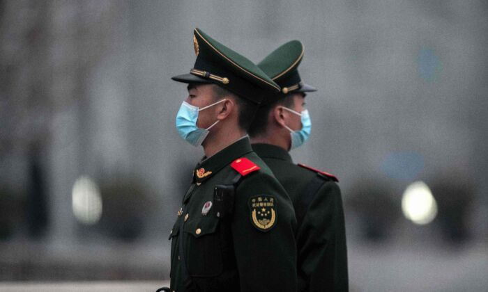 Chinese soldiers stand guard near Tiananmen Square in Beijing on March 5, 2021. (Nicolas Asfouri/AFP via Getty Images)
