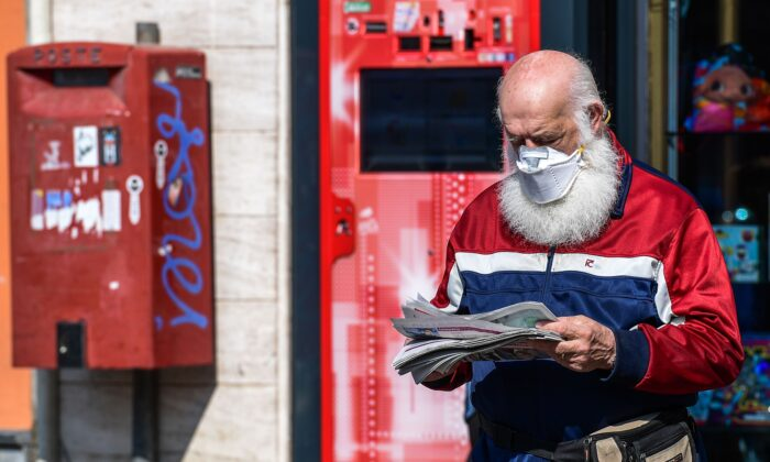 A resident wearing a face mask exits a shop after buying a newspaper in Treviolo, Italy, on April 9, 2020. (Miguel Medina/AFP via Getty Images)