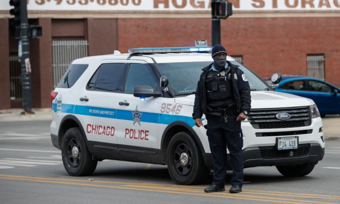 A Chicago Police officer monitors the scene after a shooting in Chicago, Ill., on March 14, 2021. (Kamil Krzaczynski/AFP via Getty Images)