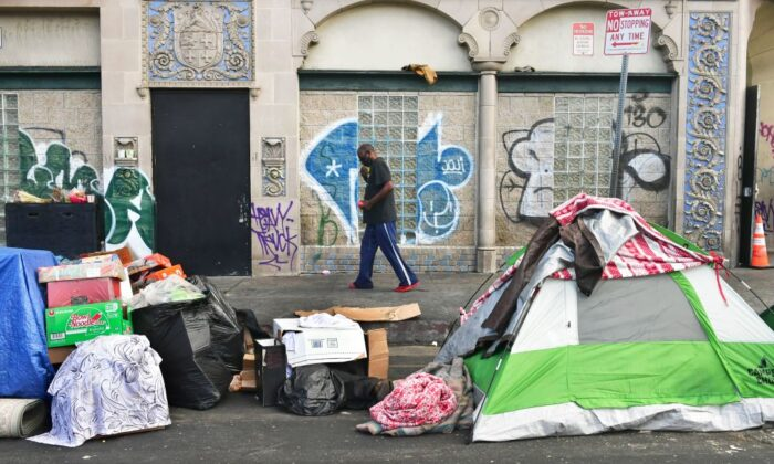 A man walks past tents housing the homeless on the streets in the Skid Row community of Los Angeles, Calif. on April 26, 2021. (Frederic J. Brown/AFP via Getty Images)