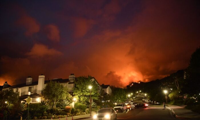 Flames from the Palisades fire glow in the distance in Topanga, northwest of Los Angeles, on May 15, 2021.   Patrick T. Fallon/AFP via Getty Images)