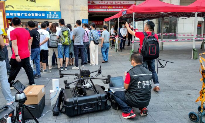 A staff member of the Emergency Management Department (front) works with a drone in front of the SEG Plaza in Shenzhen, China, on May 19, 2021, a day after it triggered widespread panic when it began shaking and was evacuated. (AFP via Getty Images)