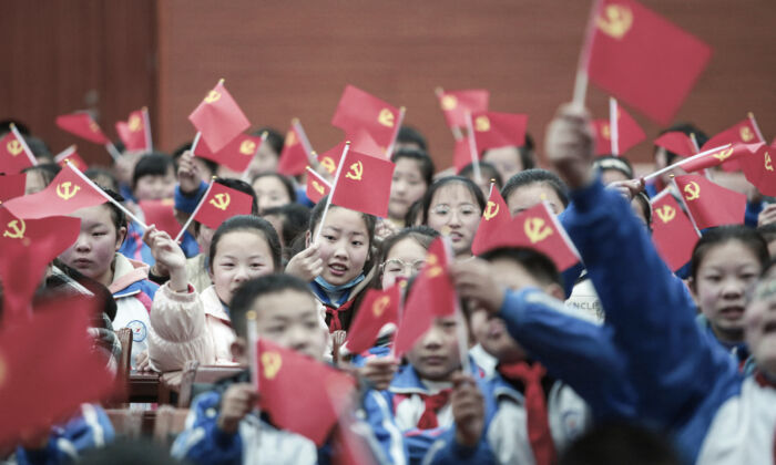 """Students wave flags of the Communist Party as they prepare to watch a movie """"The Founding of a Party"""" in Yangzhou, Jiangsu Province, on March 23, 2021. (STR/AFP via Getty Images)"""