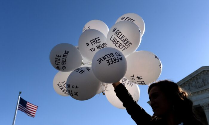 A protester holds balloons calling for religious freedom outside the U.S. Supreme Court in Washington on April 28, 2015. (Olivier Douliery/Getty Images)