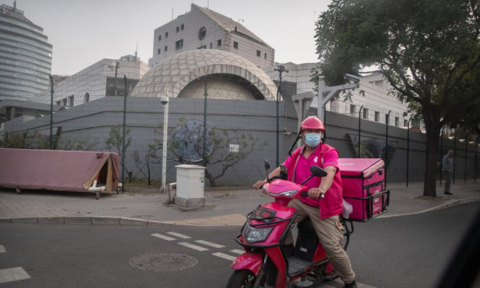 A delivery driver waits to cross an intersection near the Israeli Embassy in Beijing, on May 19, 2021. (Mark Schiefelbein/AP Photo)