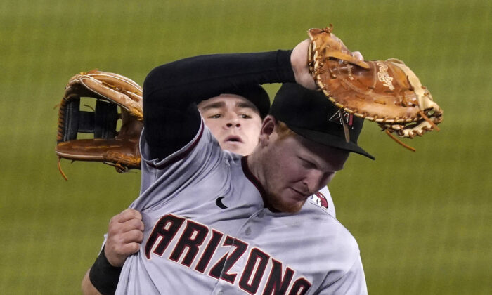 Arizona Diamondbacks first baseman Pavin Smith (R) makes a catch on a ball hit by Los Angeles Dodgers' Will Smith as second baseman Andrew Young collides with him during the fifth inning of a baseball game, in Los Angeles, Calif., on May 18, 2021. (Mark J. Terrill/AP Photo)