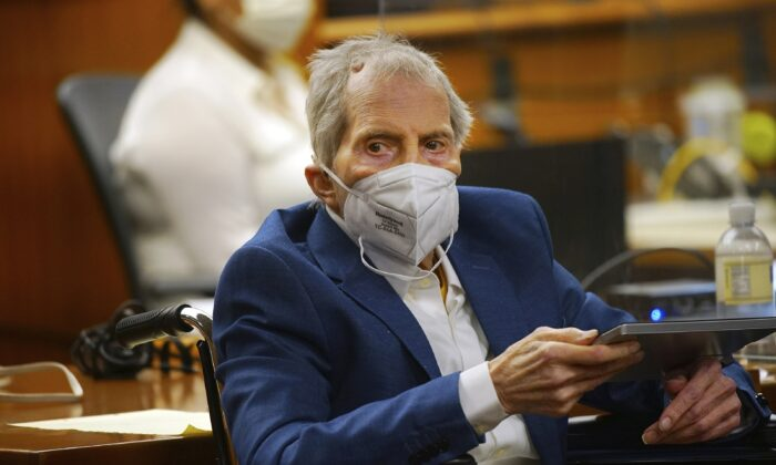 Robert Durst holds a device to read the real time spoken script as he appears in the courtroom of Judge Mark E. Windham as attorney's begin opening statements in the trial of the real estate scion charged with murder of longtime friend Susan Berman, at Los Angeles County Superior Court in Inglewood, Calif., on May 18, 2021. (Al Seib/Los Angeles Times via AP, Pool)