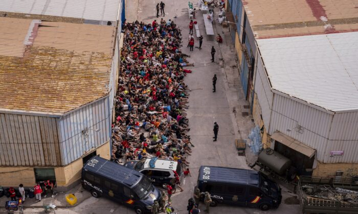 Unaccompanied minors who crossed into Spain are gathered outside a warehouse used as temporary shelter as they wait to be tested for COVID-19 at the Spanish enclave of Ceuta, near the border of Morocco and Spain, on May 19, 2021. (Bernat Armangue/AP Photo)