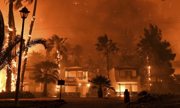Fire burns among houses during a wildfire in the village of Schinos, near Corinth, Greece, on May 19, 2021. (Valerie Gache/AP Photo)