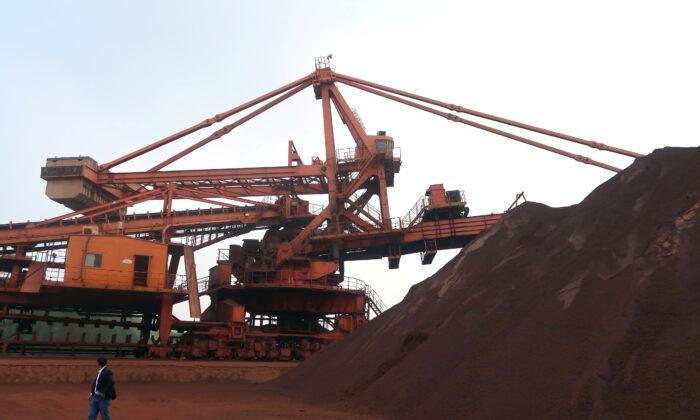 A man walks by an iron ore blending site at Dalian Port, Liaoning province, China Sept. 21, 2018. (Muyu Xu/Reuters)