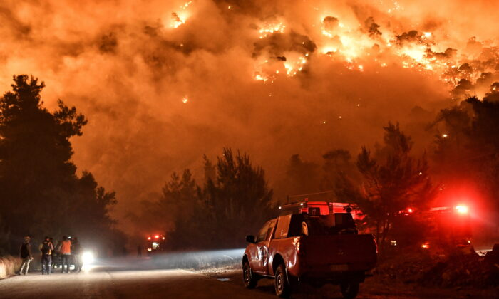 Flames rise as firefighters and volunteers try to extinguish a fire burning in the village of Schinos, near Corinth, Greece on May 19, 2021.  (Vassilis Psomas/Reuters)