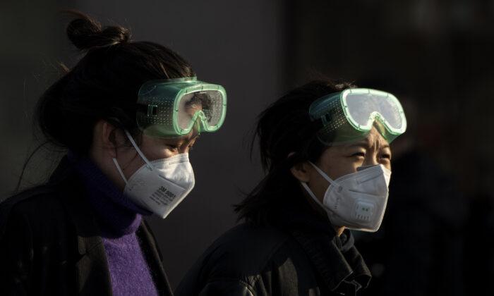 Travelers wearing masks arrive from various provinces at the Beijing Railway Station on Feb. 3, 2020. (Noel Celis/AFP via Getty Images)