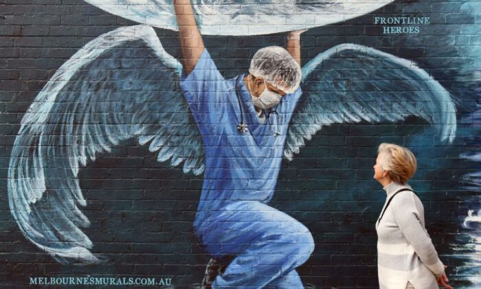 A woman looks at a mural of a health worker with wings holding a globe on International Nurses Day in Melbourne on May 12, 2020.(Photo by WILLIAM WEST/AFP via Getty Images)