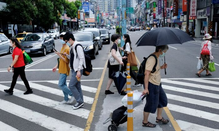 Pedestrians wear protective masks after a new wave of COVID-19 occurred in New Taipei city on May 15, 2021. (Sam Yeh/AFP via Getty Images)