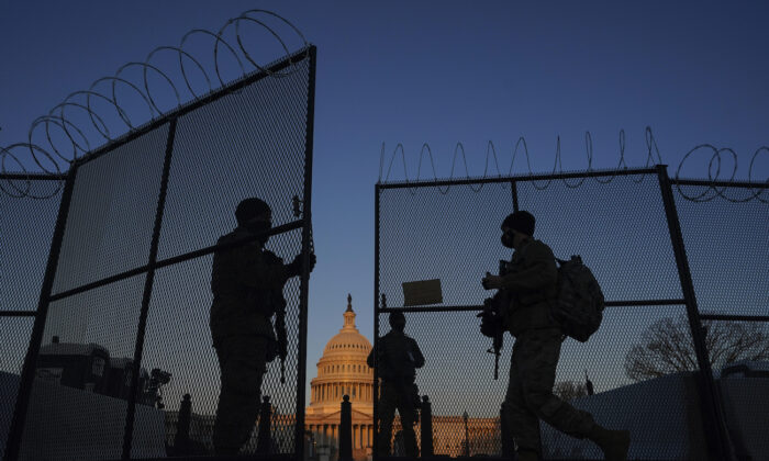 Members of the National Guard open a gate in the razor wire topped perimeter fence around the Capitol at sunrise in Washington, on March 8, 2021. (AP Photo/Carolyn Kaster)