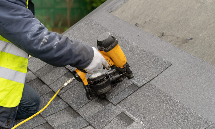 Tearing the old shingles off is the most difficult part of re-roofing a house. Laying the new shingles is actually a pretty straightforward, simple job for most homeowners. (brizmaker/Shutterstock)