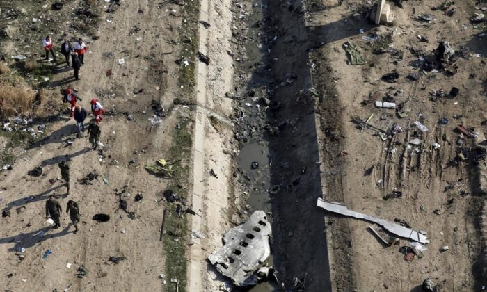 Rescue workers search the scene where a Ukrainian plane crashed in Shahedshahr, southwest of the capital Tehran, Iran, on Jan. 8, 2020. An Ontario court has ruled that the Iranian military's downing of a passenger jet early last year was an intentional act of terrorism, paving the way for relatives of those killed to seek compensation from the country. (The Canadian Press/AP-Ebrahim Noroozi)