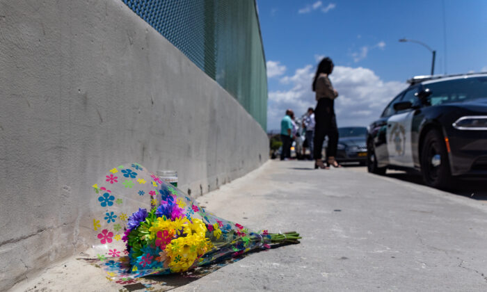 Officers, civilians, and media stand on an overpass next to an area on the 55 Freeway where a shooting believe to have been prompted by road rage killed a six-year-old boy May 21, 2021 in Orange, Calif. (John Fredricks/The Epoch Times)