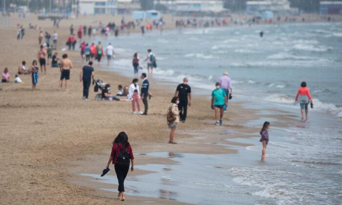 People walk in the beach of Valencia, Spain, on May 9, 2021. (Jose Jordan/AFP via Getty Images)