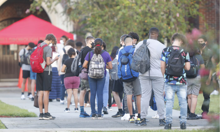 High school students wait in line to have temperature checked before entering campus in a file photo. (Octavio Jones/Getty Images)