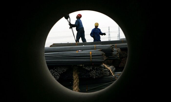 Workers unload steel at a steel products exchange market in Shanghai, China on Apr. 6, 2005. (Photo by China Photos/Getty Images)