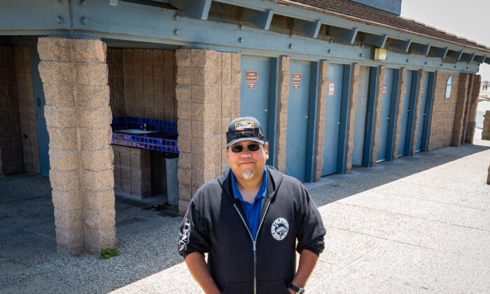 Rolando Galvan stands near the public restrooms by lifeguard tower 13 in Huntington Beach, Calif., on May 20, 2021. (John Fredricks/The Epoch Times)