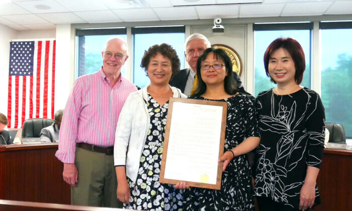 Robert F. Babyok, Jr. (C), chairman of Louisa County board of supervisors, and local resident hold the resolution condemning forced organ harvesting in China, in Louisa County, Va., on May. 17, 2021. (Sherry Dong/The Epoch Times)