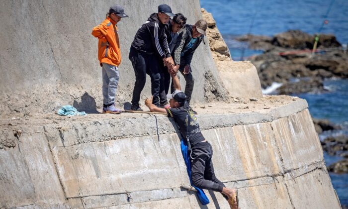 Migrants climb a sea wall in the northern town of Fnideq after attempting to cross the border from Morocco to Spain's North African enclave of Ceuta on May 19, 2021. (Fadel Senna/AFP via Getty Images)