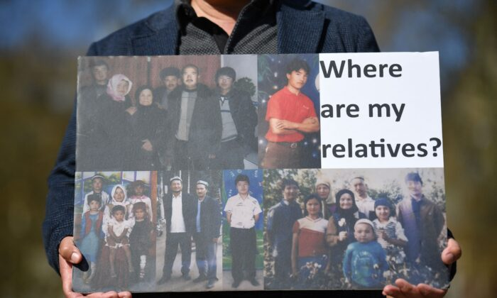 A member of the Uyghur community holds a placard as he joins a demonstration to call on the British parliament to vote to recognize alleged persecution of China's Muslim minority Uyghur people as genocide and crimes against humanity in London on April 22, 2021. (Justin Tallis/AFP via Getty Images)