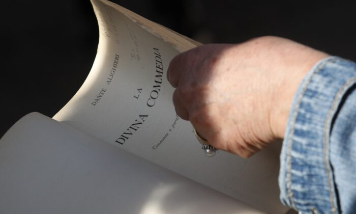 """Ravenna citizen Giuliana Turati holds a copy of the Divina Commedia """"Divine Comedy"""" by poet Dante Alighieri as she listens to a reading by volunteer Carlotta Zangolli in front of Alighieri's tomb, in Ravenna, Italy, on May 8, 2021. (Antonio Calanni/AP Photo)"""