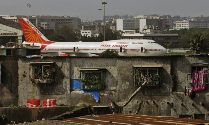 An Air India plane is seen in the background of slums adjoining the the international airport in Mumbai, India, on May 25, 2010. (Rajanish Kakade/AP Photo)