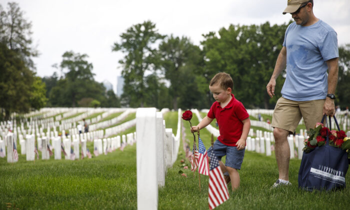Matthew Murphy, 4, places a rose on a tombstone beside his father, Kevin Murphy, of Springfield, Va., during a volunteer event at Arlington National Cemetery ahead of Memorial Day on May 26, 2019, in Arlington, Va. (Tom Brenner/Getty Images)