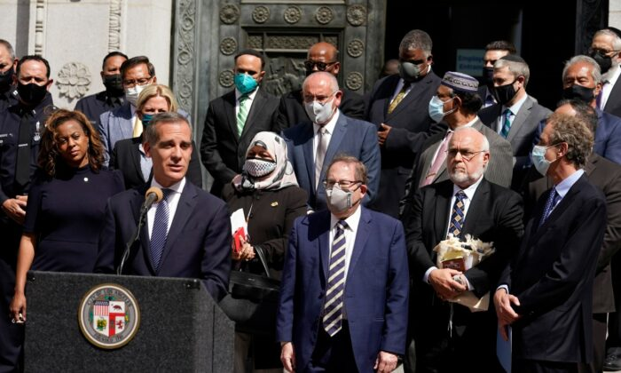 Los Angeles Mayor Eric Garcetti, at podium, speaks in front of civic and faith leaders outside City Hall in Los Angeles, Calif., on May 20, 2021. (Marcio Jose Sanchez/File/AP Photo)