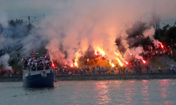A boat with players cruises on Sava river as Red Star fans celebrate after their team won the Serbian soccer league title in Belgrade, Serbia, on May 22, 2021. (Darko Vojinovic/AP Photo)
